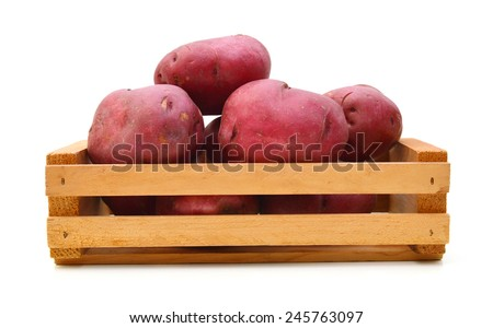 New potato tuber heap isolated in wooden crate on white background cutout