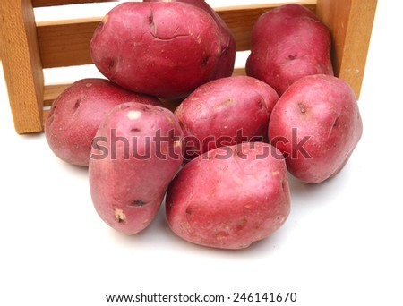 New potato tuber heap isolated in wooden crate on white background cutout  - stock photo