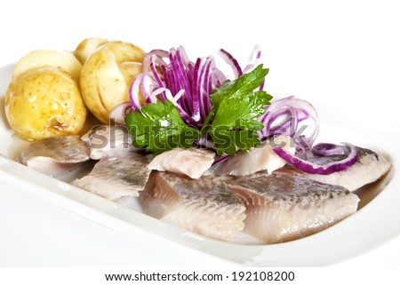 New potatoes, pickled herring, red onion and parsley twig - stock photo