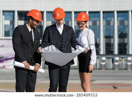 New project. A group of three architects are looking forward while standing on the street in construction helmets and holding blueprints in hand. Business team