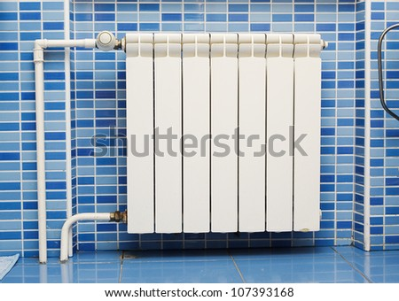 New radiator on blue wall - stock photo
