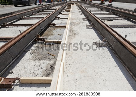 new railway tracks near a busy street in a city with cars on the road - stock photo