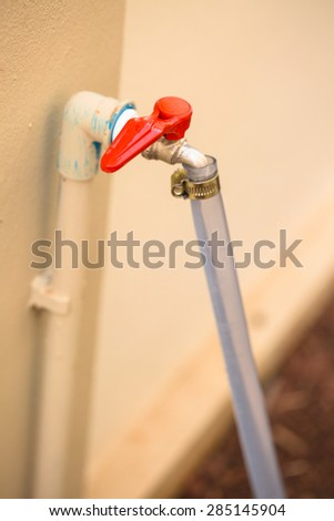 New red faucet with rubber tube - stock photo