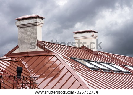 new red metal roof with skylights and chimneys - stock photo