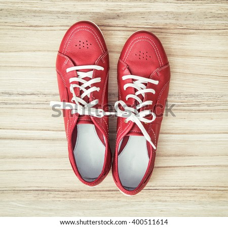New red women's leather shoes on the wooden background. Beauty and fashion. View from above.