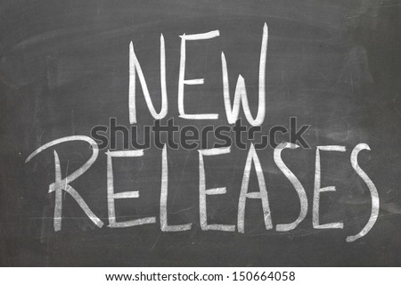 New Releases word in white chalk handwriting on the blackboard - stock photo