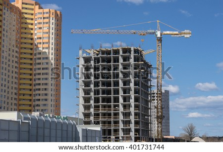 New residential building and construction building big hoisting tower crane - stock photo