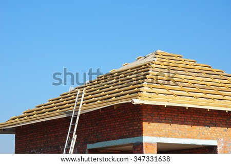 New Roof Membrane Coverings with Wooden Construction Home Framing with Roof Rafters and Ladder Outdoor against Blue Sky. Roofing Construction Exterior.