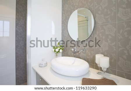 New round sink and mirror with stainless steel faucet - stock photo