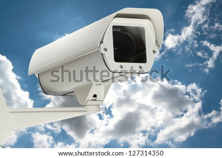 New security camera with cloudy sky as a background. - stock photo