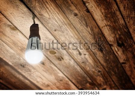 New Shining LED Light Bulb installed in an Old Socket to E27 Light Bulbs on Wooden Ceiling - stock photo