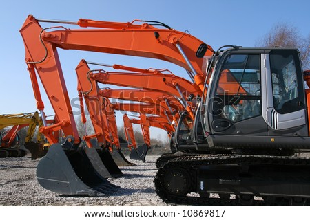 New, shiny and modern orange excavator machines. Construction industry machinery.