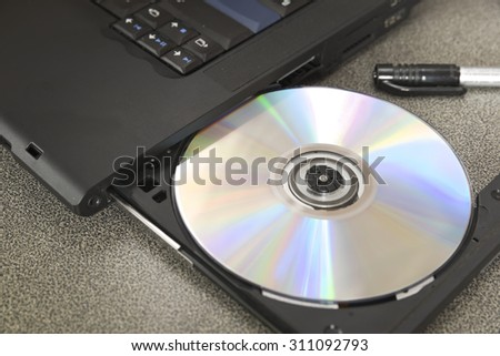 New shiny CD/DVD inside optical disk drive bay of black laptop