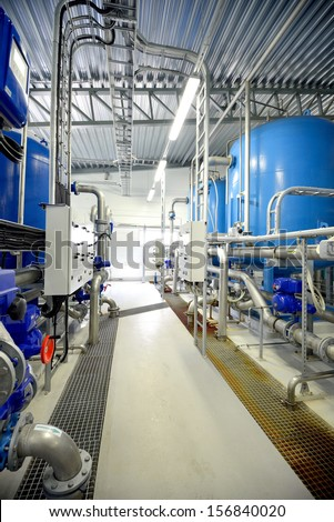 new shiny pipes and large tanks in industrial boiler room - stock photo