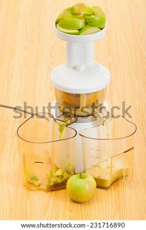 new slow juicer making apple organic juice - stock photo
