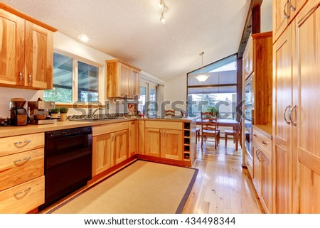 New Solid wood acacia kitchen custom made cabinets with hardwood floor. Large open space with vaulted ceiling. - stock photo