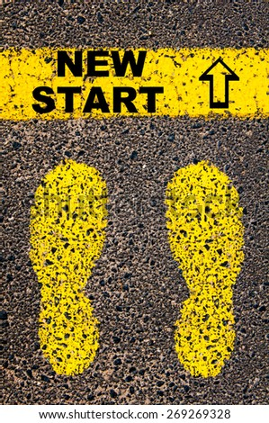 New Start message. Conceptual image with yellow paint footsteps on the road in front of horizontal line over asphalt stone background. - stock photo