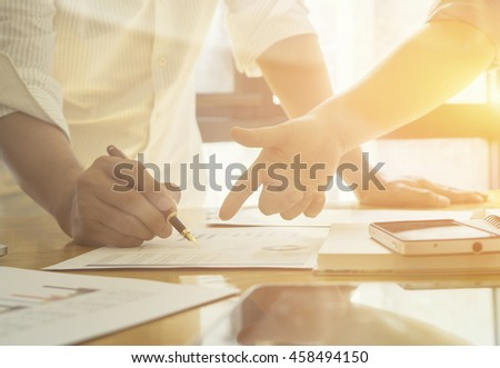 New startup business project,Business meeting time,account managers crew working with new startup project,pointing hands,Laptop Notebook on wood table.analyze plans,vintage tone,morning light flare - stock photo