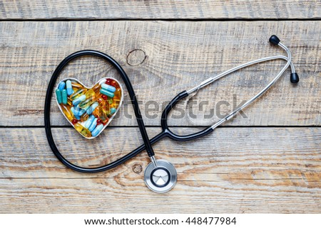 new stethoscope on wooden table with pills close up - stock photo