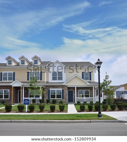 New Stone and Siding Town Homes for Sale Suburban Residential Neighborhood Blue Sky Clouds - stock photo