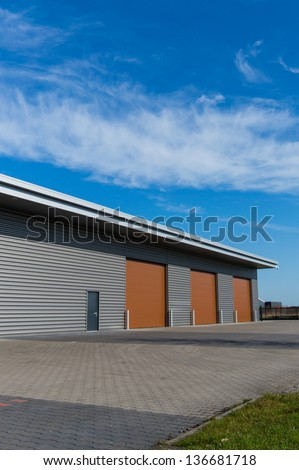 new storage warehouse with brown doors and blue sky - stock photo