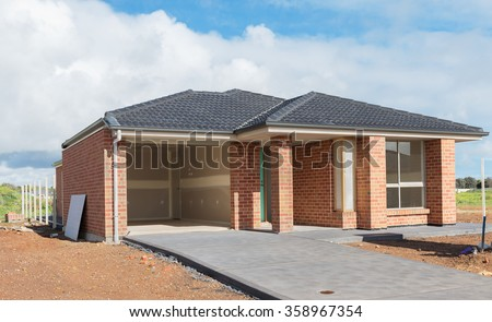 new suburban home currently under construction against cloudy sky - stock photo