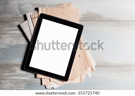 New tablet and newspapers  - stock photo