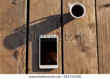 New tablet PC and coffee on wooden table at sunset. - stock photo