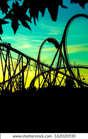 new thematic park and entertainment park. silhouette of rollercoaster at fair - stock photo