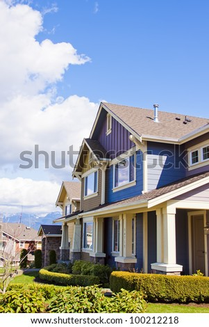 new townhouses or condominiums with blue sky and clouds - stock photo