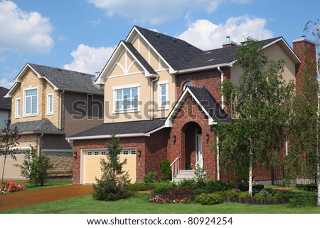 New two-storied beige brick cottage with garage at sunny day. - stock photo