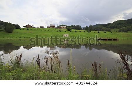 New village near pond in the Altai, Russia - stock photo