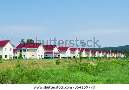 New village of similar houses, built along the road. Summer Sunny day. Russia - stock photo