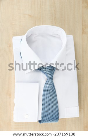 New white man's shirt with color tie on wooden background - stock photo