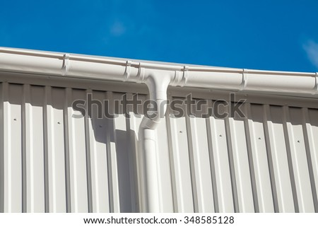 New white rain gutter on a building with white metal sheet against blue sky