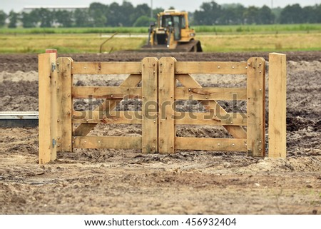 New wooden Fence on wasteland in front of a Bulldozer working on a construction site. - stock photo