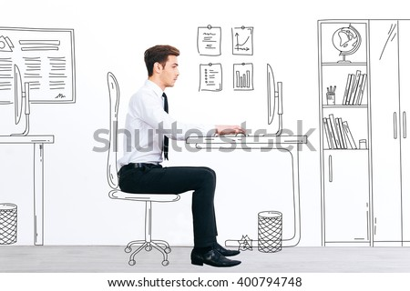 New working day. Side view of handsome young man working with drawn computer while sitting at his illustrated working place - stock photo