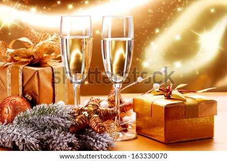 New Year and Christmas Celebration. Two Champagne Glasses and Gifts over Golden Blinking Holiday Background