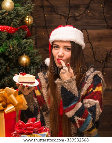 New Year and Christmas concepts. Beautiful girl eating delicious cake while sitting near New Year tree and Christmas presents and gifts.