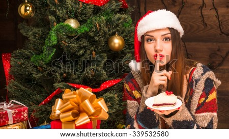 New Year and Christmas concepts. Beautiful girl sitting near New Year tree and holding a delicious piece of cake in front of her.