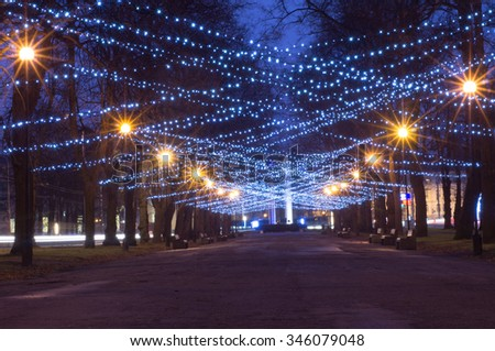 New Year and Christmas festoon illumination on city alley - stock photo