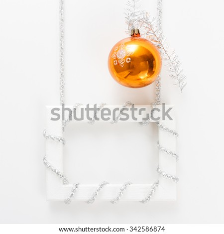 New Year and Christmas greeting card template made of horizontal white frame with silver tinsel and orange ball  - stock photo
