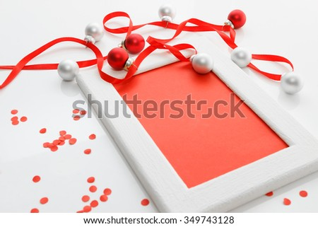 New Year and Christmas greeting card template made of white frame and red card with red ribbon, silver and red balls and red confetti, horizontal  view