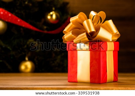New Year and Christmas present or gift with gold ribbon represented on the wooden table in front of New Year tree. - stock photo
