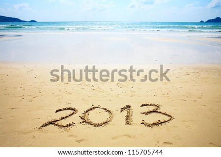 "New year background of beach with ""2013"" drawn in the sand - stock photo"