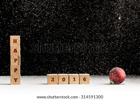 New Year 2016 background with falling snow and a red Christmas bauble with the word Happy spelled out on stacked wooden blocks with the date 2016 alongside over black with copyspace for your greeting. - stock photo