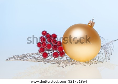 New Year background with golden glass toy  and branch of rowan on silver decorative leaf - stock photo