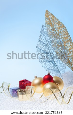 New Year background with golden glass toys and little presents with decorative leafs - stock photo