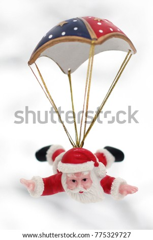 New Year card. New Year's toy. Santa Claus is flying with a parachute. New Year