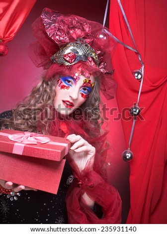 New Year Carnival. Portrait of young woman with present box. - stock photo